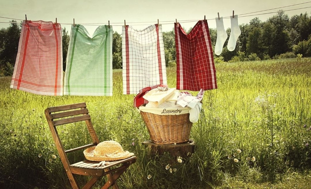 laundry hung on clothesline with laundry basket, wooden chair, and straw hat, country field in background