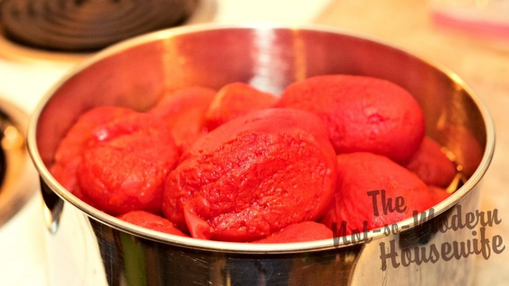 Skinned tomatoes can be kept in a large bowl while they wait to be chopped before adding to homemade salsa.